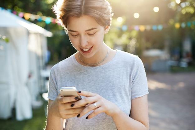 Vrouw met behulp van slimme telefoon. portret van een jong hipsterwijfje met behulp van een moderne slimme telefoon buitenshuis texting