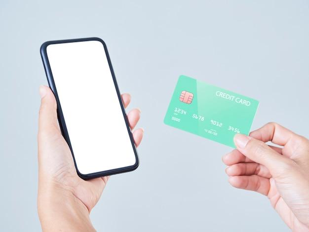 Vrouw met behulp van smartphone en creditcard voor online winkelen, betalingen of cheques bankrekening.