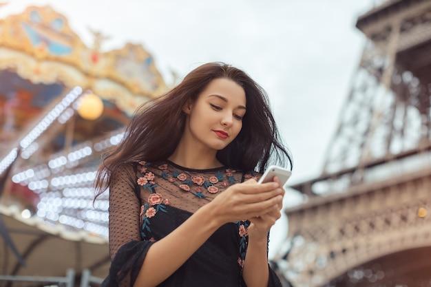 Vrouw met behulp van smartphone in de buurt van de eiffeltoren en carrousel, parijs reizen.