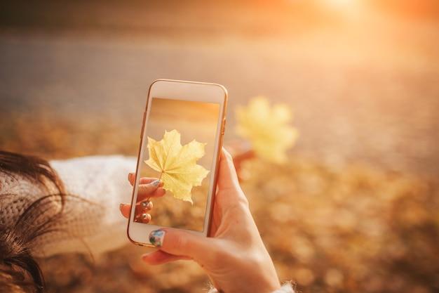Vrouw met behulp van smartphone in de herfst