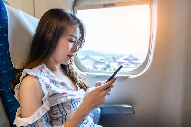 Vrouw met behulp van smartphone in de trein.