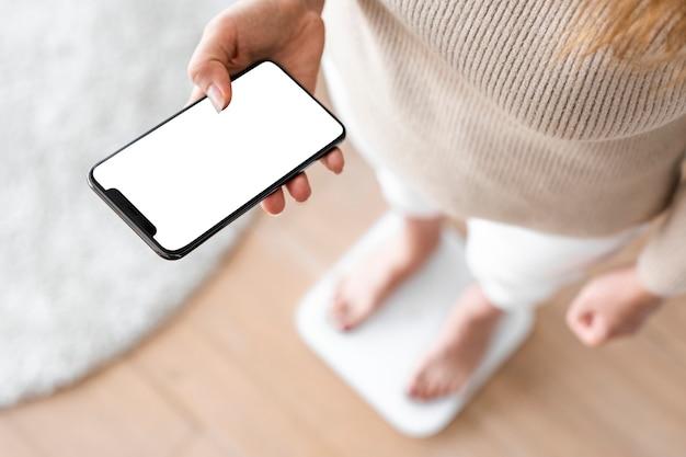 Vrouw met behulp van smartphone naast de innovatieve technologie van de weegschaal