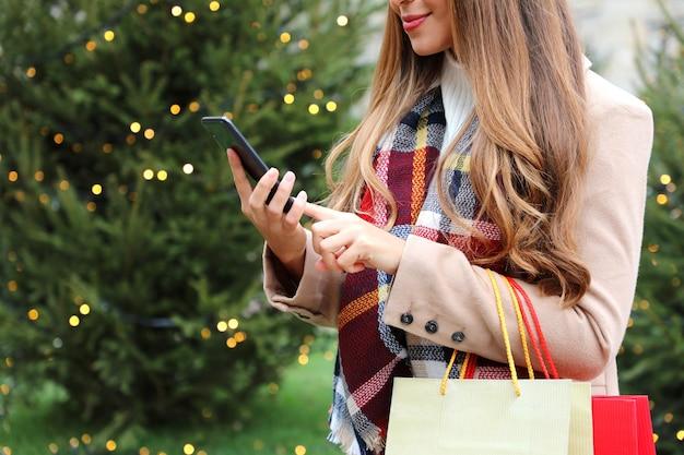 Vrouw met behulp van smartphone om online te winkelen en draagtassen