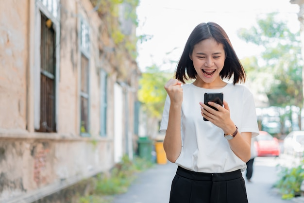 Vrouw met behulp van smartphone voor de toepassing en het tonen van een gelukkig gebaar.