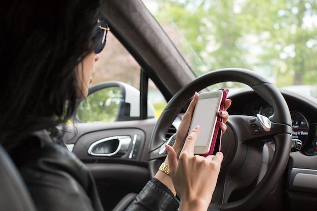 Vrouw met behulp van smartphone. wazig auto-interieur