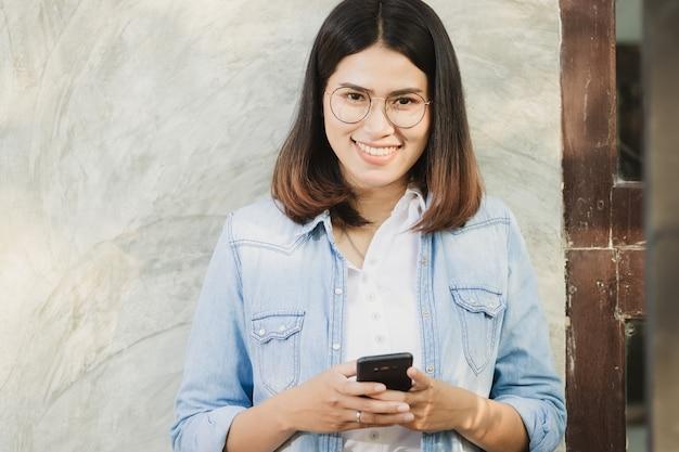 Vrouw met behulp van smartphone werken in vrije tijd met gelukkig.