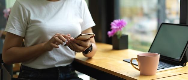 Vrouw met behulp van smartphone zittend aan de werktafel met mock-up tablet