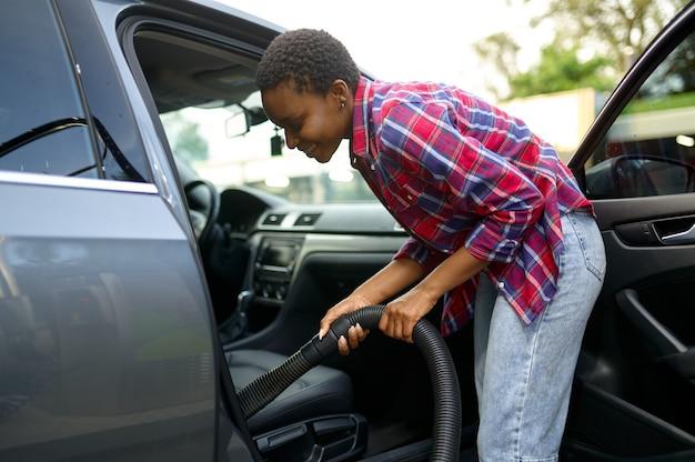 Vrouw met behulp van stofzuiger, hand car wash station. autowasindustrie of bedrijf. vrouwelijke persoon reinigt haar voertuig van vuil buitenshuis