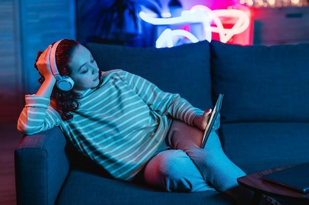 Vrouw met behulp van tablet en koptelefoon thuis op de bank