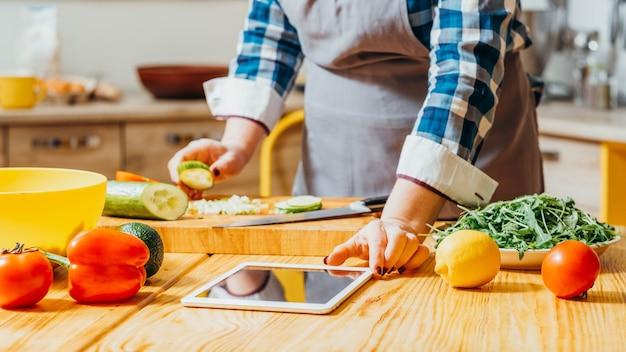 Vrouw met behulp van tablet voor het controleren van recepten tijdens het koken in de keuken