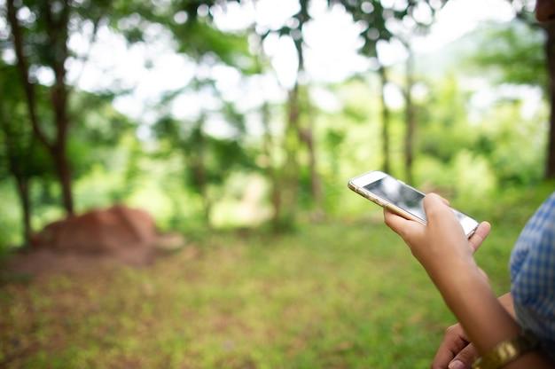 Vrouw met behulp van telefoon in het bos