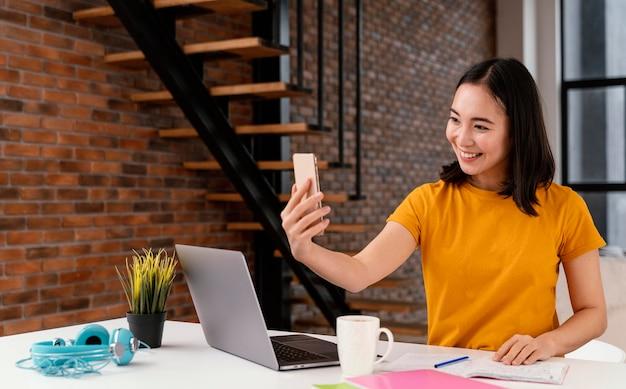 Vrouw met behulp van telefoon tijdens het bijwonen van online les
