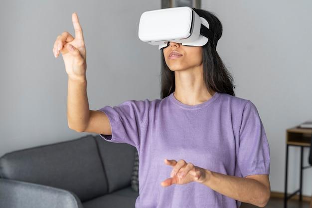 Vrouw met behulp van virtual reality headset thuis met laptop
