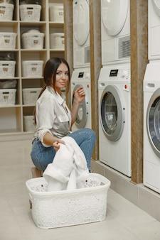 Vrouw met behulp van wasmachine de was te doen. jonge vrouw klaar om kleren te wassen. interieur, wasproces concept