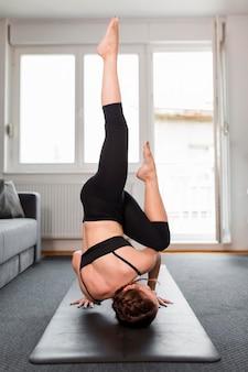 Vrouw met benen omhoog sport thuis concept