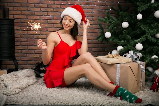 Vrouw met bengaals licht door de kerstboom