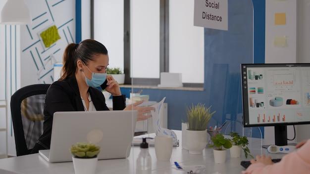 Vrouw met beschermend gezichtsmasker die op laptopcomputer in bedrijfskantoor werkt en statistieken controleert terwijl ze aan het telefoneren zijn. teamwerkers die sociale afstand respecteren om infectie met covid19-virus te voorkomen