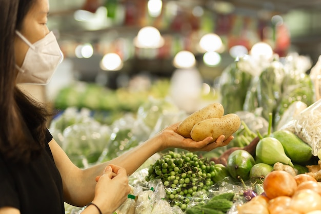 Vrouw met beschermend masker die aardappel vasthoudt in groentewinkel