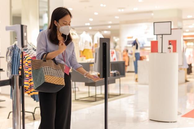 Vrouw met beschermend masker die automatische alcoholgel gebruikt die haar hand schoonmaakt voordat ze het winkelcentrum binnengaat