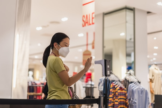 Vrouw met beschermend masker die de temperatuur van de thermometer meet terwijl ze het winkelcentrum binnengaat.