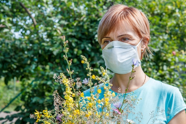 Vrouw met beschermend masker die een boeket van wilde bloemen vasthoudt en probeert allergieën voor stuifmeel te bestrijden. vrouw die haar neus beschermt tegen allergenen. allergie concept.