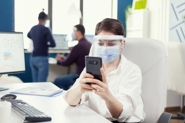 Vrouw met beschermend masker die in een professionele werkruimte aan het typen op een mobiele telefoon achter de computer werkt