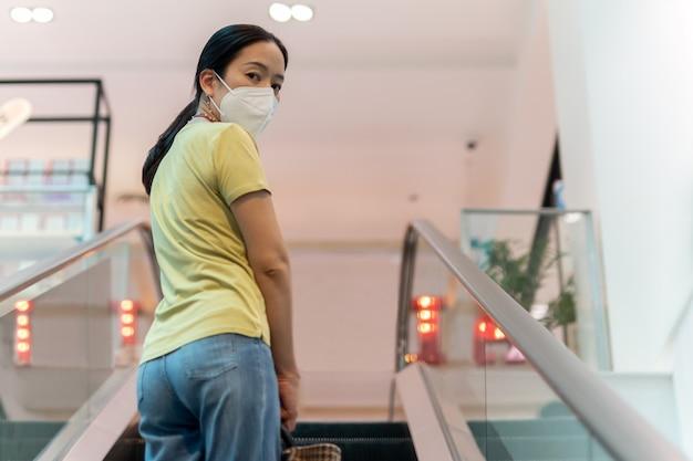 Vrouw met beschermend masker die terugkijkt op de camera.