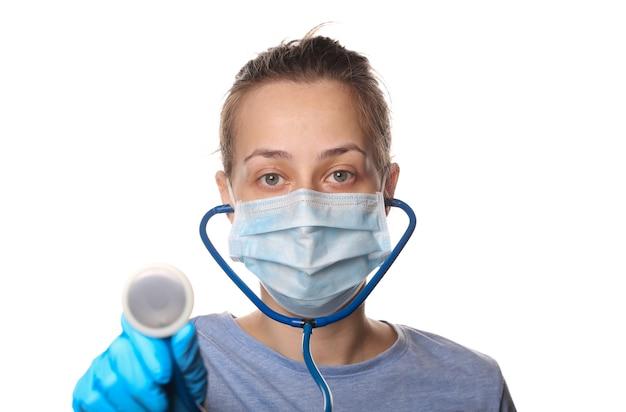 Vrouw met beschermend masker, handschoenen houdt een stethoscoop vast die op wit wordt geïsoleerd