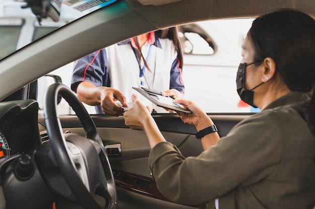 Vrouw met beschermend masker in een auto die benzine met creditcard betaalt bij benzinestation.
