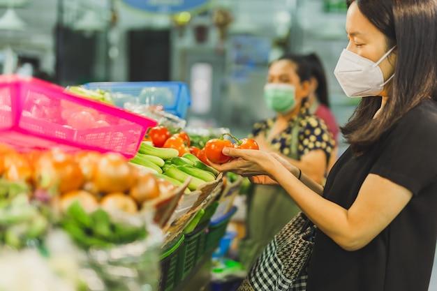 Vrouw met beschermend masker kiest tomaat in groentewinkel