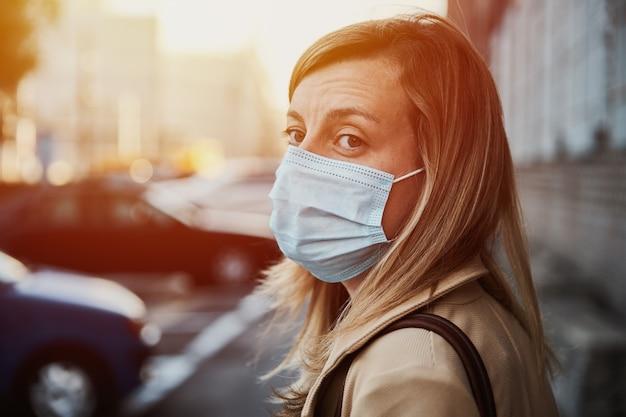 Vrouw met beschermend masker op stadsstraat
