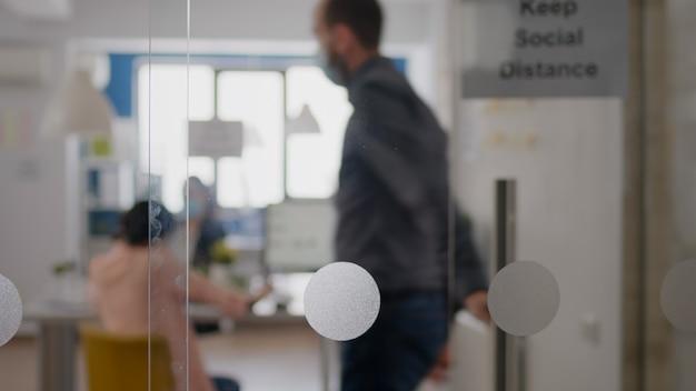 Vrouw met beschermend medisch gezichtsmasker die aan de telefoon praat terwijl collega's aan de computer werken, met respect voor de sociale afstand in het startbureau om infectie met coronavirus te voorkomen