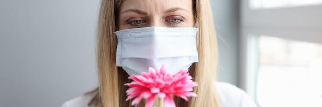 Vrouw met beschermend medisch masker die bloem snuift