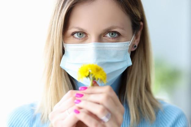 Vrouw met beschermend medisch masker die gele bloem snuift
