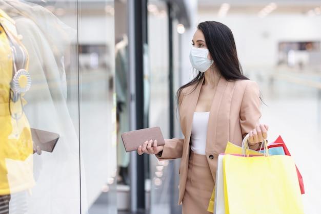 Vrouw met beschermend medisch masker kijkt naar vitrine met kleding in winkelcentrum