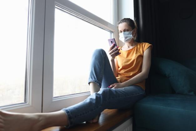Vrouw met beschermend medisch masker zittend op de vensterbank met mobiele telefoon in haar handen