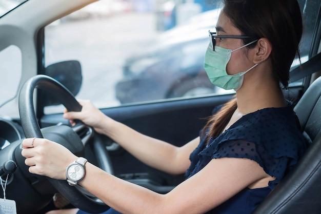 Vrouw met beschermende gezichtsmasker auto, tegen coronavirus