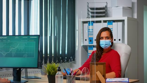 Vrouw met beschermingsmasker dat werkt en kijkt naar de camera die achter de pc zit. werknemers in de werkruimte in een zakelijk bedrijf typen op het toetsenbord van de computer en kijken naar het bureaublad met inachtneming van sociale afstand
