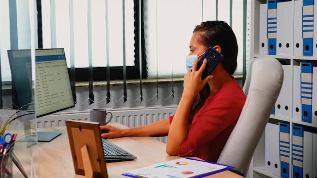Vrouw met beschermingsmasker die afspraken maakt met behulp van mobiele telefoon. freelancer die op een nieuwe, normale werkplek werkt en op een smartphone spreekt met collega's op afstand die naar de desktop kijken die de klantenlijst analyseert