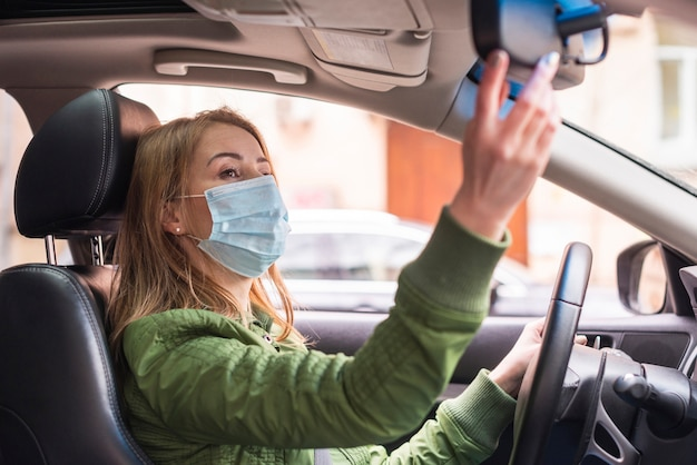 Vrouw met beschermingsmasker in haar auto