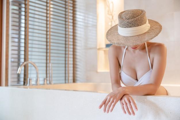 Vrouw met bikini en strohoed die betrekking hebben op het gezicht ontspannen in het bubbelbad. spa behandelingen