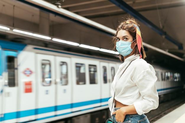 Vrouw met blauw chirurgisch masker te wachten in treinstation tegen metro.