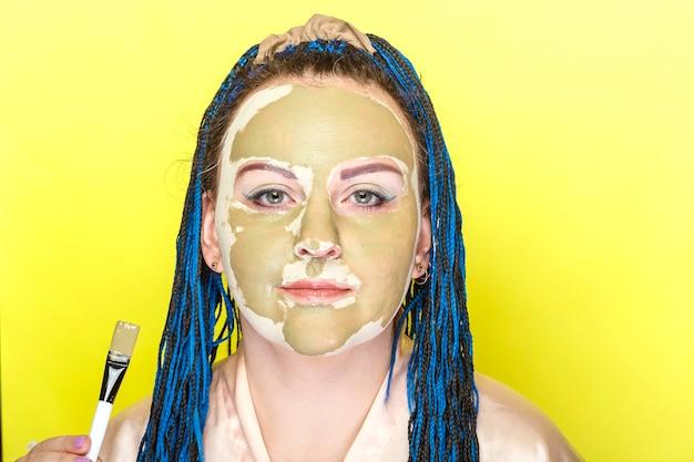 Vrouw met blauw vlechtengezicht in een masker van groene klei