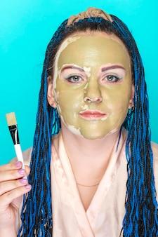 Vrouw met blauwe afro vlechten gezicht in een masker van groene klei op een blauwe achtergrond houdt een penseel in haar handen