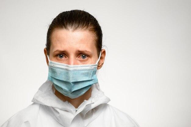 Vrouw met blauwe ogen en droevige uitdrukking in medische masker voor bescherming tegen griep.