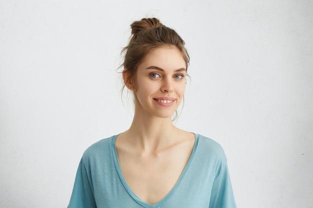 Vrouw met blauwe ogen kijken met een glimlach naar de camera