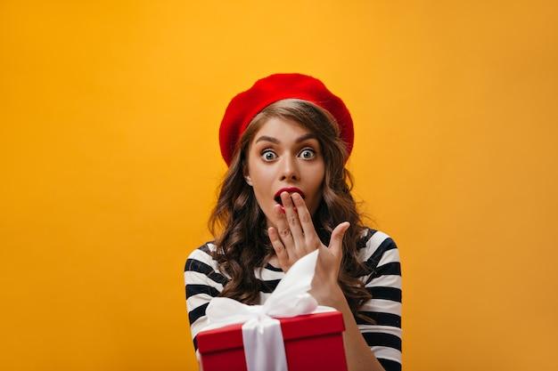 Vrouw met blauwe ogen kijkt geschokt en krijgt aanwezig. verrast meisje met krullend haar in rode baret en gestreept overhemd houdt geschenkdoos.