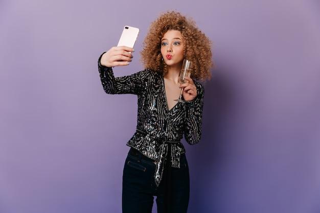 Vrouw met blauwe oogschaduw die donkere jeans en glanzende discotop draagt, stelt op paarse ruimte. meisje houdt glas champagne, blaast kus en neemt selfie.