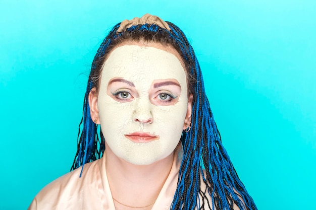 Vrouw met blauwe vlechten gezicht in een bevroren masker gemaakt van groene klei