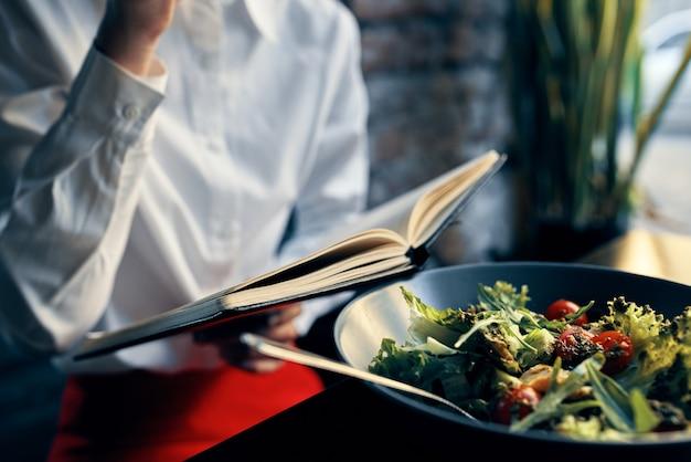 Vrouw met blocnote bij het venster en salade in een plaat tomaten verse groenten